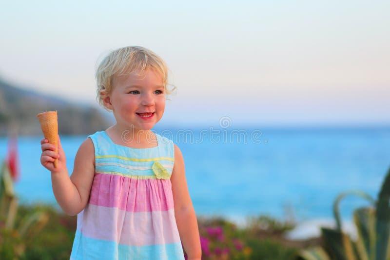 Καλό μικρό κορίτσι που τρώει το παγωτό στην παραλία στοκ εικόνες