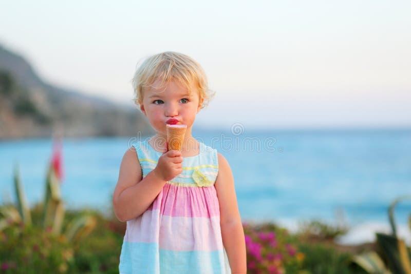 Καλό μικρό κορίτσι που τρώει το παγωτό στην παραλία στοκ φωτογραφία με δικαίωμα ελεύθερης χρήσης