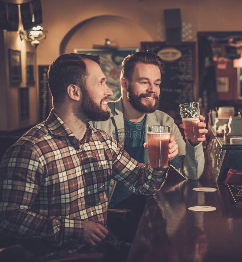 Καλύτερα riends που πίνουν την μπύρα σχεδίων στο μετρητή φραγμών στο μπαρ στοκ φωτογραφία με δικαίωμα ελεύθερης χρήσης