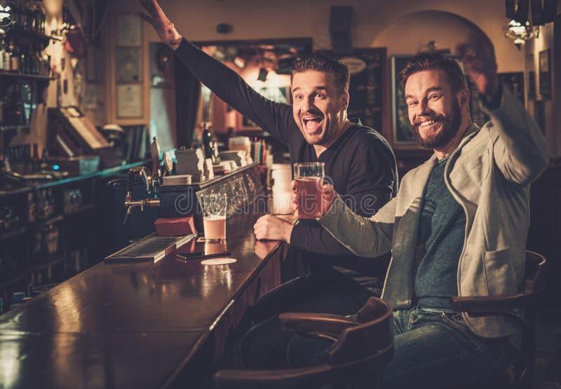 Καλύτεροι φίλοι που έχουν τη διασκέδαση που προσέχει ένα ποδοσφαιρικό παιχνίδι στη TV και που πίνει την μπύρα σχεδίων στο μετρητή στοκ εικόνες