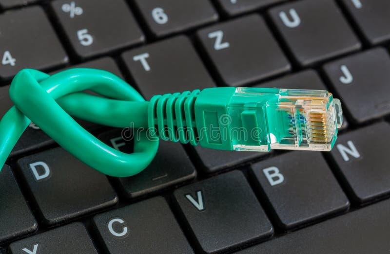 Καλώδιο δικτύων με τον πράσινους κόμβο και το πληκτρολόγιο στοκ φωτογραφίες