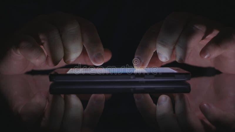 Κείμενο ατόμων που χρησιμοποιεί την οθόνη τηλεφωνικής αφής κυττάρων στη σκοτεινή σύνδεση στο Διαδίκτυο πρόσβασης γραφείων στοκ εικόνα με δικαίωμα ελεύθερης χρήσης