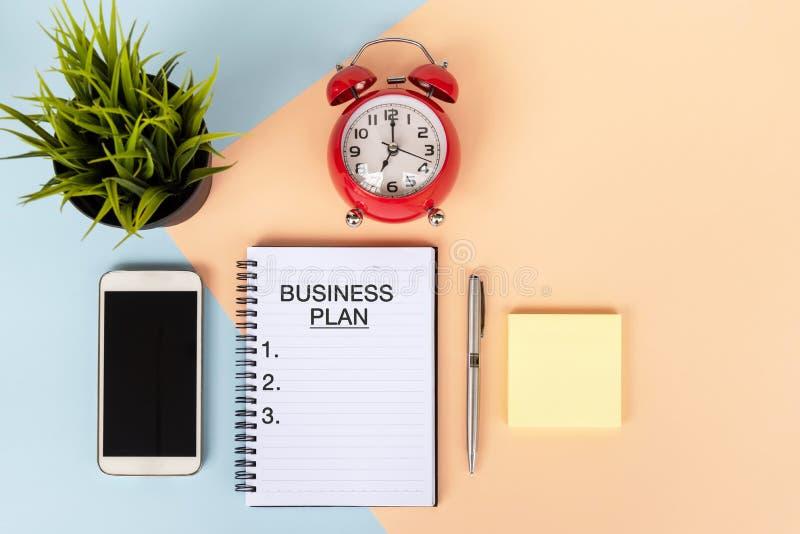 Κείμενο επιχειρηματικών σχεδίων στο σημειωματάριο με το ξυπνητήρι, το έξυπνο τηλέφωνο, τη μάνδρα και τις σε δοχείο εγκαταστάσεις  στοκ φωτογραφίες