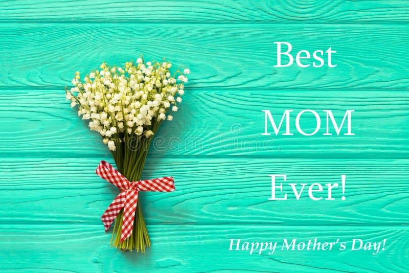 Κείμενο ημέρας της ευτυχούς μητέρας στο μπλε αγροτικό ξύλινο υπόβαθρο το επίπεδο λουλουδιών άνοιξη έννοιας ευχετήριων καρτών βρέθ στοκ φωτογραφίες με δικαίωμα ελεύθερης χρήσης