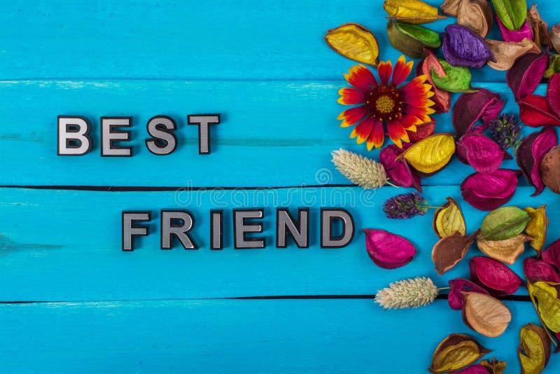 Κείμενο καλύτερων φίλων στο μπλε ξύλο με το λουλούδι στοκ φωτογραφία με δικαίωμα ελεύθερης χρήσης