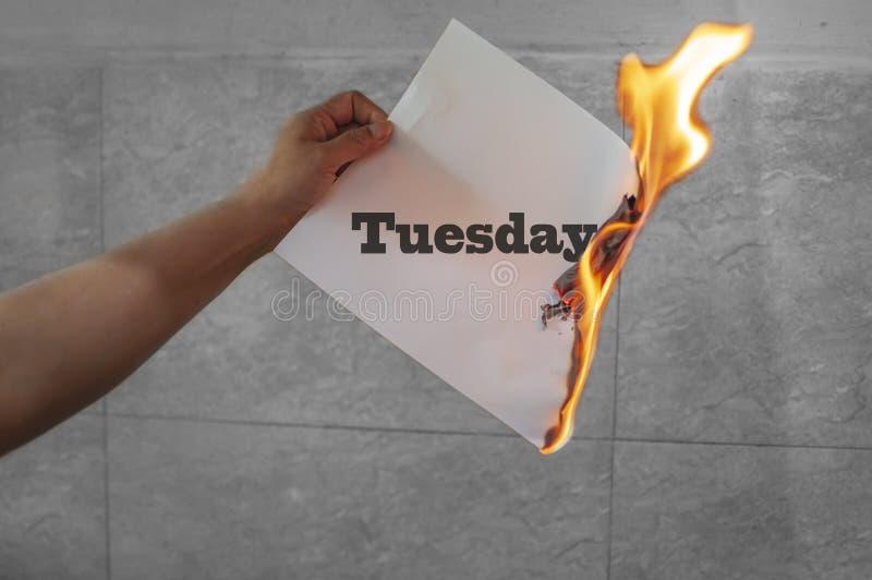 Κείμενο λέξης Τρίτης στην πυρκαγιά με το κάψιμο του εγγράφου στοκ εικόνες