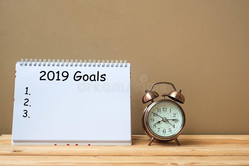 Κείμενο 2019 στόχων στο σημειωματάριο και αναδρομικό ξυπνητήρι στο διάστημα πινάκων και αντιγράφων στοκ εικόνα