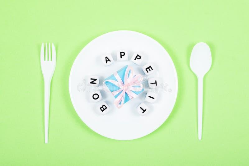 Κείμενο Bon appetit στο στρογγυλό άσπρο πιάτο με το κιβώτιο δώρων, κουτάλι, δίκρανο στο πράσινο υπόβαθρο Εορταστικός, γενέθλια, κ στοκ φωτογραφία με δικαίωμα ελεύθερης χρήσης