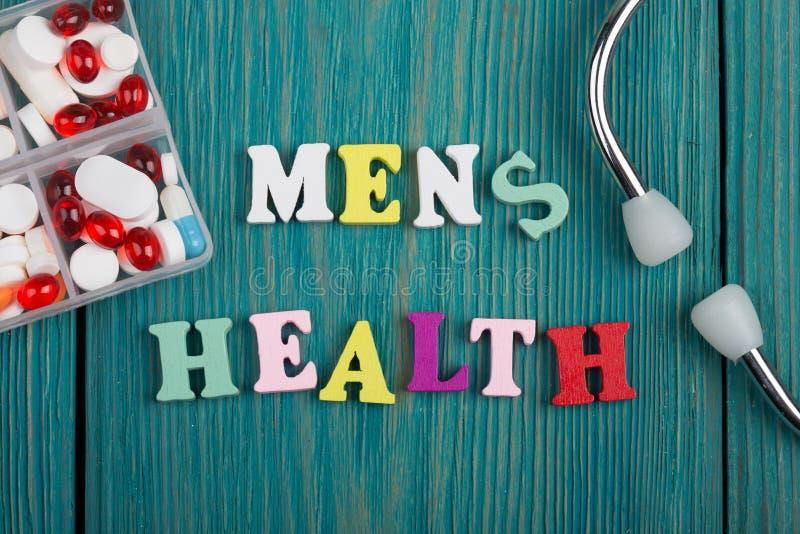 Κείμενο & x22 Men& x27 s health& x22  από τις χρωματισμένα ξύλινα επιστολές, το στηθοσκόπιο και τα χάπια στοκ φωτογραφία