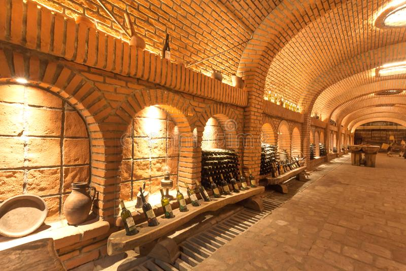 Κελάρι κρασιού και πολλά μπουκάλια με τα παλαιά ζυμωνομμένα ποτά της οινοποιίας Khareba, με τη σήραγγα πετρών στοκ εικόνες