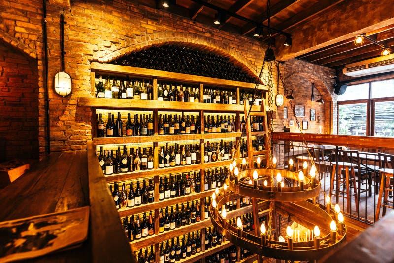 Κελάρι κρασιού στον τοίχο στα ιταλικά εστιατόριο που διακοσμείται με το τούβλο στο θερμό φως που δημιούργησε την άνετη ατμόσφαιρα στοκ εικόνες