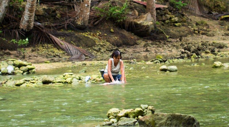 Κεμπού, Φιλιππίνες - 6 Ιουνίου 2017: Τα φτωχά ενδύματα πλύσης γυναικών στον ποταμό στοκ εικόνα