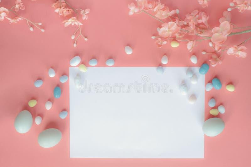 Κενά κάρτα και λουλούδια καραμελών βύνης αυγών Πάσχας κρητιδογραφιών πέρα από ένα χρωματισμένο κοράλλι υπόβαθρο στοκ φωτογραφίες με δικαίωμα ελεύθερης χρήσης