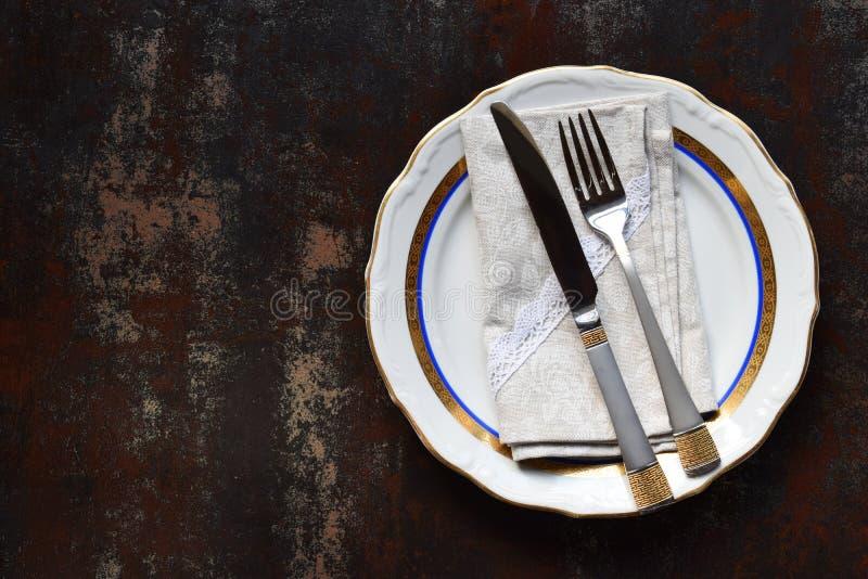 Κενά κεραμικά πιάτα και μαχαιροπήρουνα Επιτραπέζιο σκεύος στο σκοτεινό υπόβαθρο Επιτραπέζια ρύθμιση r Χλεύη επάνω, έννοια για το  στοκ εικόνες με δικαίωμα ελεύθερης χρήσης