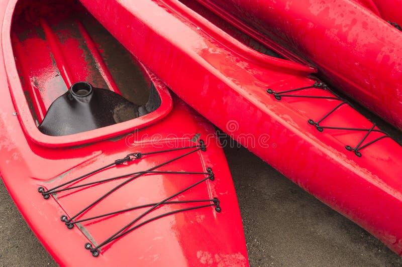 Κενά κόκκινα πλαστικά ψυχαγωγικά καγιάκ για το μίσθωμα ή τη μίσθωση, που αποθηκεύεται στην αμμώδη παραλία μετά από τις ώρες μια β στοκ φωτογραφία