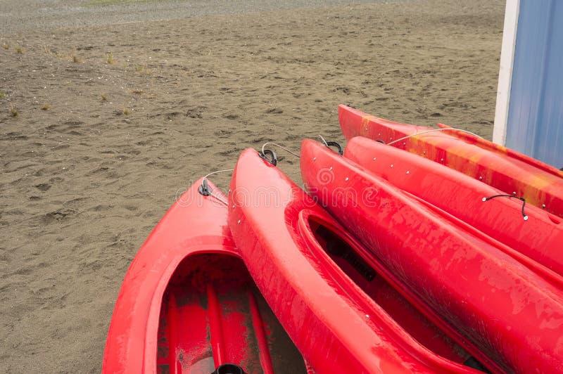 Κενά κόκκινα πλαστικά ψυχαγωγικά καγιάκ για το μίσθωμα ή τη μίσθωση, που αποθηκεύεται στην αμμώδη παραλία μετά από τις ώρες μια β στοκ εικόνες