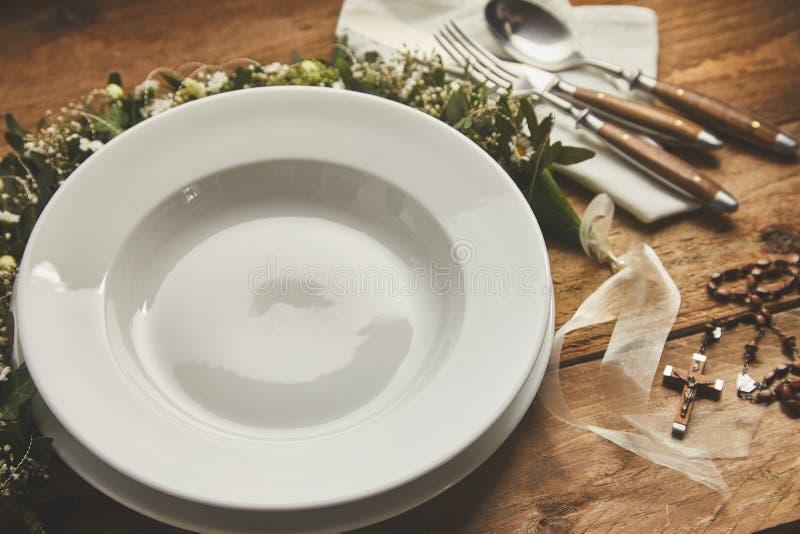 Κενά πιάτο, πιάτο και μαχαιροπήρουνα με τα χριστιανικά σύμβολα για το βάπτισμα ή την ιερή κοινωνία στοκ εικόνες