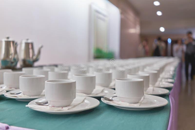 Κενά φλιτζάνια του καφέ σε μια σειρά στο ξενοδοχείο διασκέψεων στοκ εικόνα
