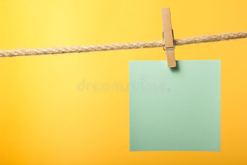 Κενές σημειώσεις εγγράφου που κρεμούν στο σχοινί με τις καρφίτσες ενδυμάτων, διάστημα αντιγράφων στοκ εικόνες