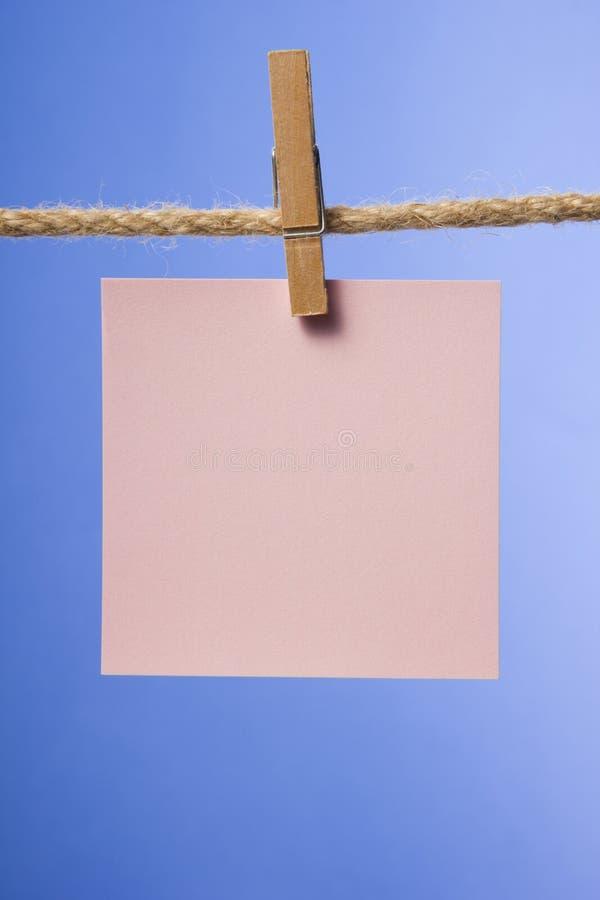 Κενές σημειώσεις εγγράφου που κρεμούν στο σχοινί με τις καρφίτσες ενδυμάτων, διάστημα αντιγράφων στοκ φωτογραφία