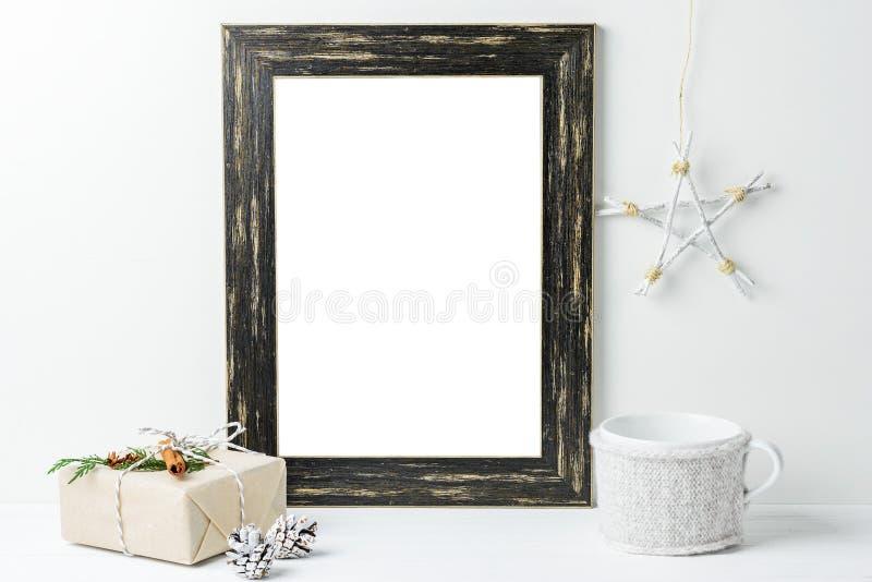 Κενή άσπρη χλεύη πλαισίων επάνω Μαύρο ξύλινο πρότυπο πλαισίων με τις διακοσμήσεις Χριστουγέννων σε ένα άσπρο υπόβαθρο στοκ φωτογραφίες