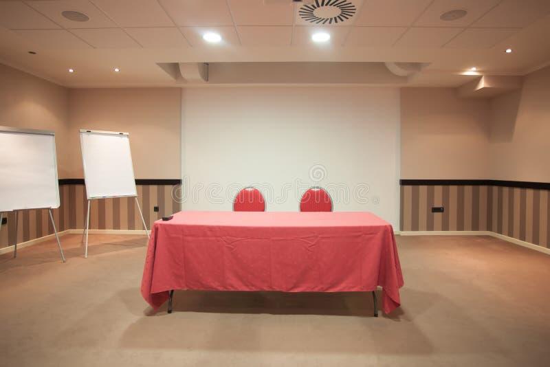Κενή αίθουσα συνδιαλέξεων με τον κόκκινο πίνακα στοκ εικόνες