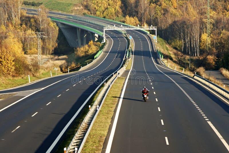 Κενή εθνική οδός που οδηγεί πέρα από τη γέφυρα πέρα από την κοιλάδα, μοτοσικλέτα, ηλεκτρονικές πύλες φόρου στοκ φωτογραφία