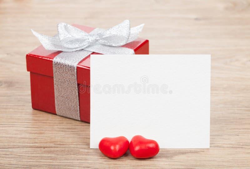 Κενή ευχετήρια κάρτα βαλεντίνων και μικρό κόκκινο κιβώτιο δώρων στοκ εικόνα