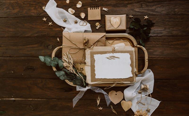 Κενή ευχετήρια κάρτα με το φάκελο του Κραφτ και χρυσές διακοσμήσεις στο ξύλινο υπόβαθρο γάμος σκαλοπατιών πορτρέτου φορεμάτων ένν στοκ φωτογραφία