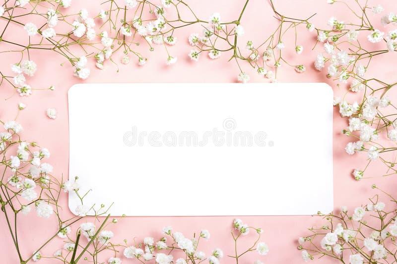 Κενή κάρτα εγγράφου με τα λεπτά μικρά άσπρα λουλούδια στη ρόδινη πλάτη στοκ φωτογραφίες