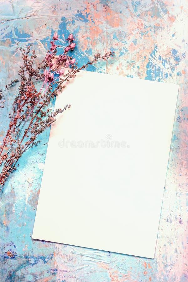 Κενή κάρτα και ξηρά λουλούδια σε παλαιό χρωματισμένο ξύλινο Backgroun στοκ εικόνα