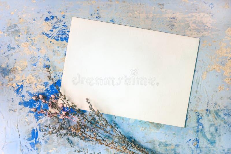 Κενή κάρτα και ξηρά λουλούδια στο μπλε ξύλινο υπόβαθρο στοκ εικόνες