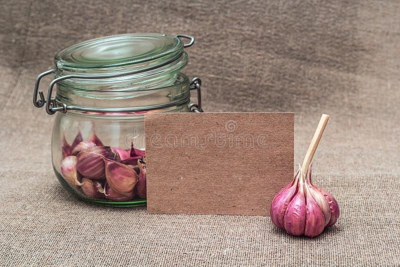 Κενή κάρτα με το σκόρδο σε ένα βάζο γυαλιού στοκ εικόνες