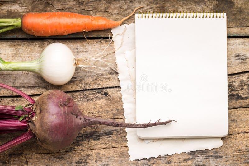 Κενή κάρτα συνταγής στο ξύλινο αγροτικό υπόβαθρο με τα φρέσκα λαχανικά στοκ φωτογραφίες