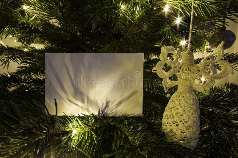 Κενή κάρτα Χριστουγέννων με το παιχνίδι αγγέλου στο χριστουγεννιάτικο δέντρο στοκ φωτογραφία με δικαίωμα ελεύθερης χρήσης
