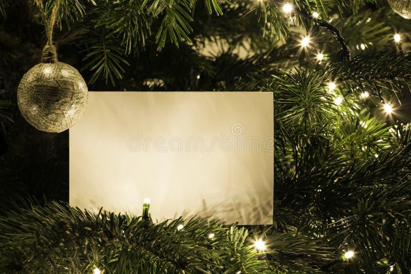 Κενή κάρτα Χριστουγέννων στο χριστουγεννιάτικο δέντρο με το παιχνίδι στοκ εικόνες