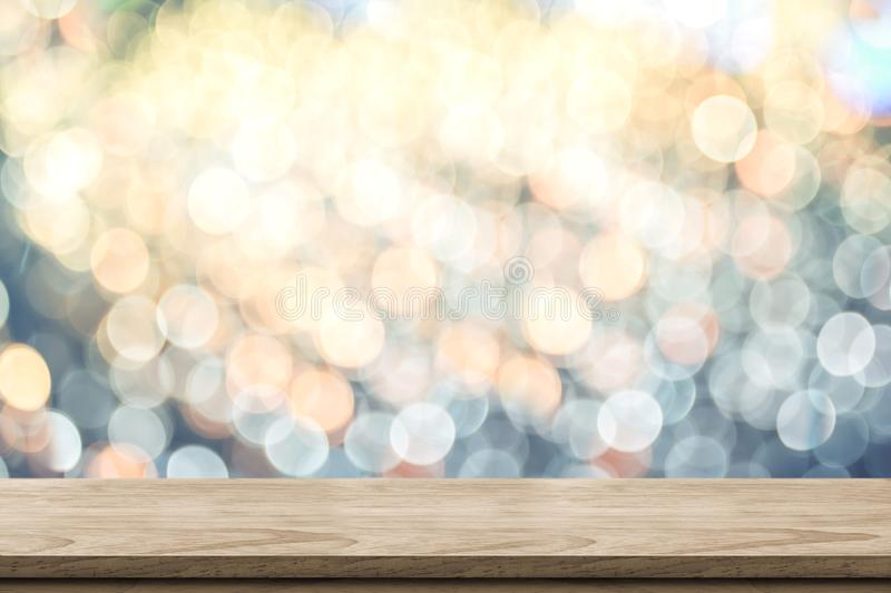 Κενή καφετιά ξύλινη επιτραπέζια κορυφή με θαμπάδων το λαμπιρίζοντας μαλακό αφηρημένο υπόβαθρο bokeh κρητιδογραφιών μπλε και πορτο στοκ εικόνα