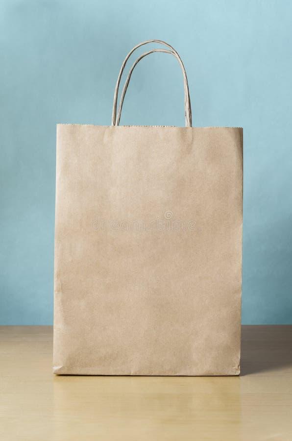 Κενή καφετιά τσάντα αγορών στον πίνακα με το μπλε υπόβαθρο στοκ εικόνα