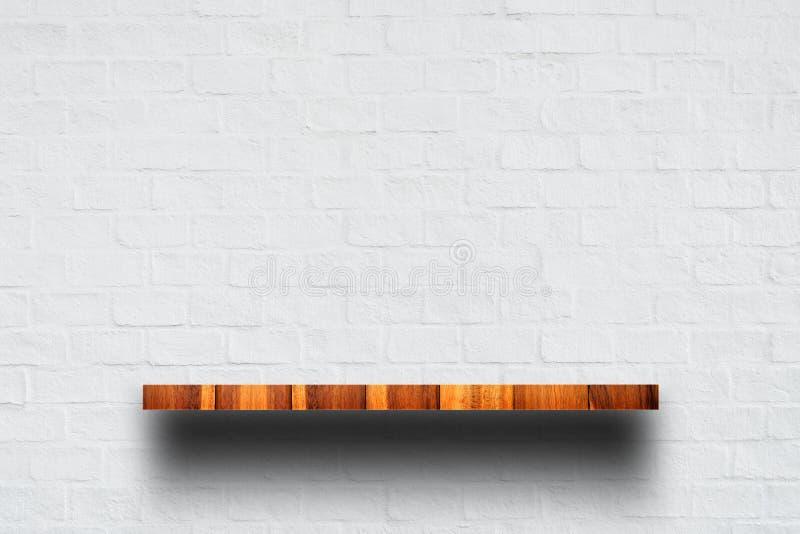 Κενή κορυφή του ξύλινου ραφιού με τον άσπρο τουβλότοιχο στοκ εικόνα