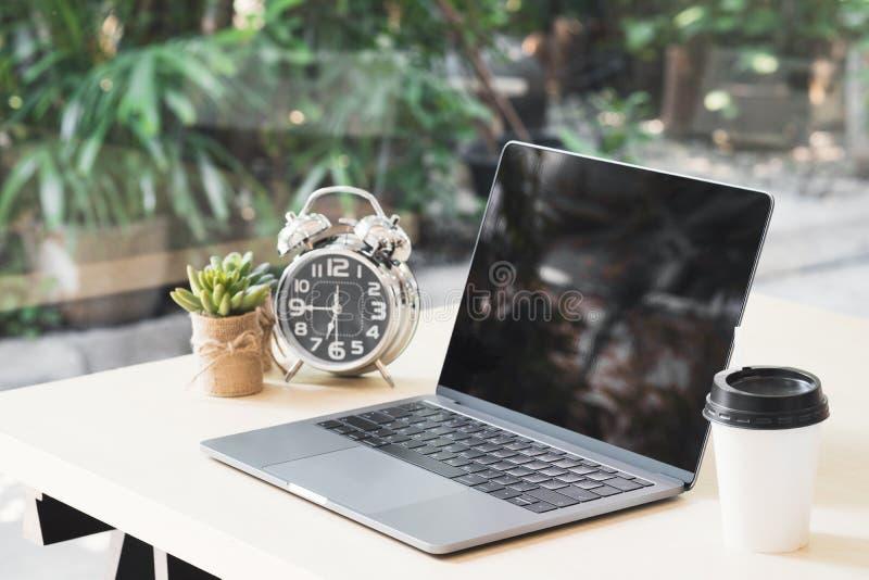 Κενή μαύρη επίδειξη οθόνης lap-top στον ξύλινο πίνακα με ένα φλυτζάνι στοκ φωτογραφία
