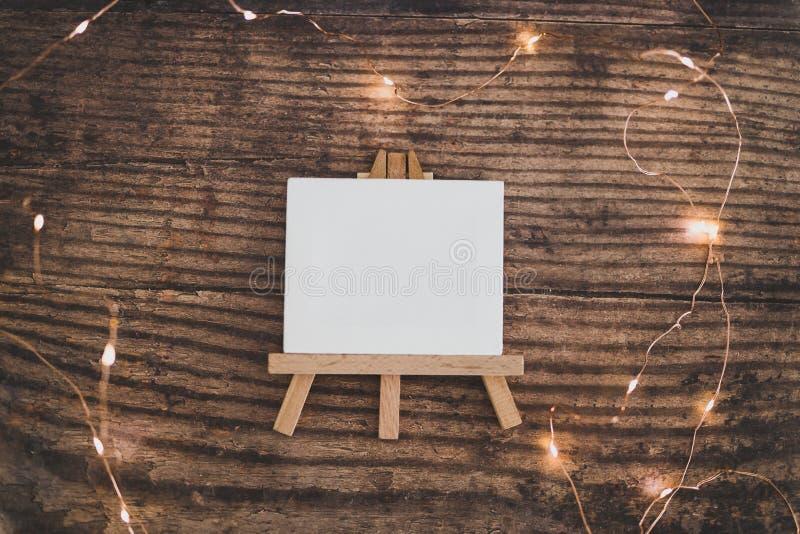 Κενή μινιατούρα καμβά περιτριγυρισμένη από νεραϊδοφώτα σε ξύλινο γραφείο στοκ φωτογραφίες με δικαίωμα ελεύθερης χρήσης