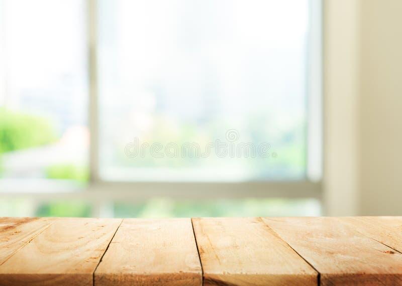 Κενή ξύλινη επιτραπέζια κορυφή στον αφηρημένο πράσινο κήπο θαμπάδων από το παράθυρο στοκ φωτογραφίες