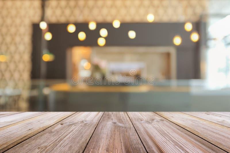 Κενή ξύλινη επιτραπέζια κορυφή με το θολωμένο εσωτερικό backgro καφετεριών στοκ εικόνες