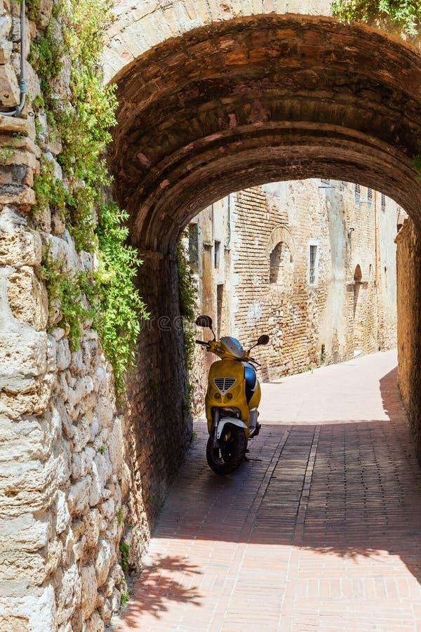 Κενή οδός στη μικρή ιταλική παλαιά πόλη με το μόνο μηχανικό δίκυκλο στοκ φωτογραφία με δικαίωμα ελεύθερης χρήσης