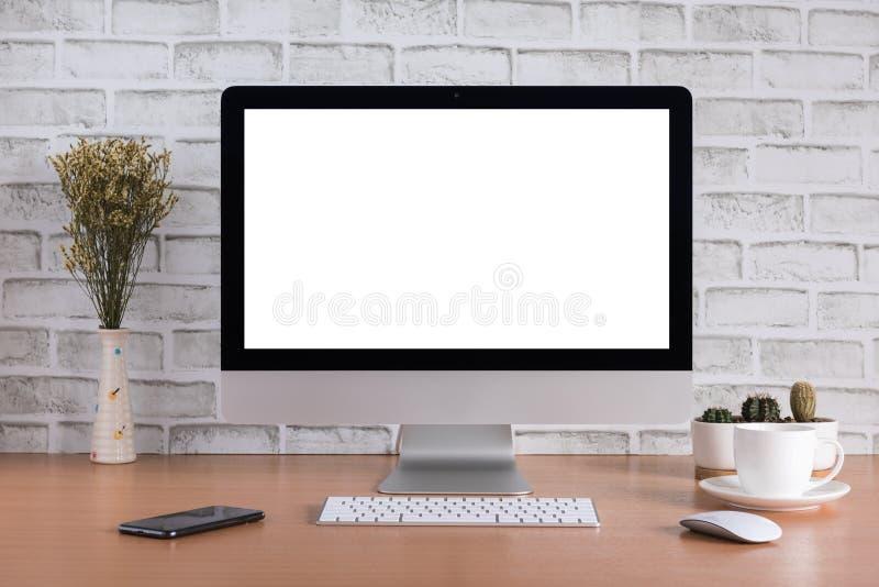 Κενή οθόνη όλοι σε έναν υπολογιστή με τα ξηρά λουλούδια, το έξυπνο τηλέφωνο, το φλυτζάνι καφέ και το βάζο κάκτων στοκ φωτογραφία