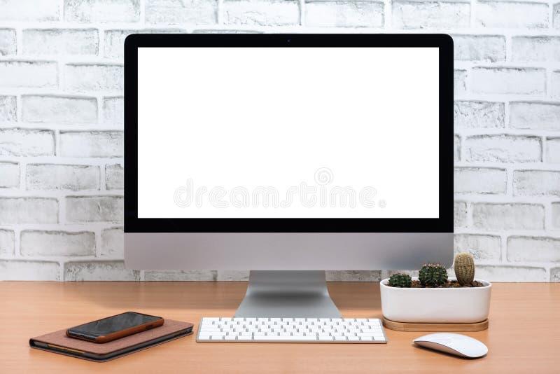 Κενή οθόνη όλοι σε έναν υπολογιστή με την ταμπλέτα, το έξυπνα τηλέφωνο και το δοχείο κάκτων στον ξύλινο πίνακα στοκ φωτογραφία με δικαίωμα ελεύθερης χρήσης