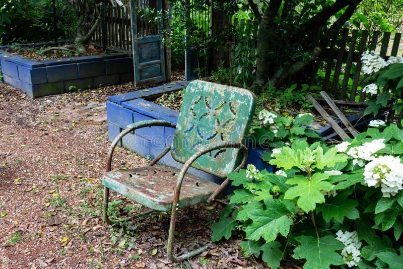 Κενή παλαιά πράσινη καρέκλα μετάλλων ενάντια σε έναν μπλε τοίχο φραγμών, έννοια απουσίας θλίψης θανάτου γήρανσης στοκ φωτογραφία