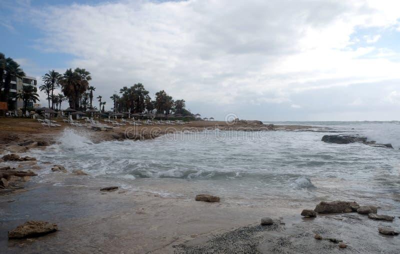 Κενή παραλία στην παραλία στη θέση θερέτρου με τα κτήρια και τους φοίνικες ξενοδοχείων στη χαμηλή εποχή στοκ εικόνες