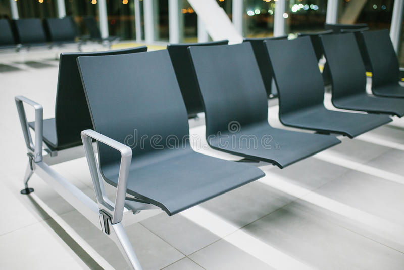 Κενή περιμένοντας περιοχή του αερολιμένα με τα καθίσματα σε μια σειρά τη νύχτα Πτήση νύχτας, μεταφορά, που περιμένει στον αερολιμ στοκ φωτογραφία