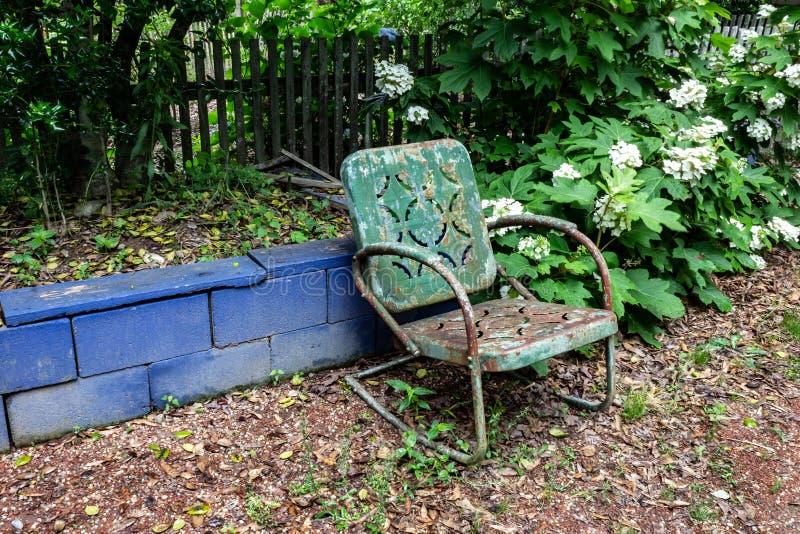 Κενή πράσινη καρέκλα μετάλλων ενάντια σε έναν μπλε τοίχο φραγμών, έννοια απουσίας θλίψης θανάτου γήρανσης στοκ φωτογραφίες με δικαίωμα ελεύθερης χρήσης